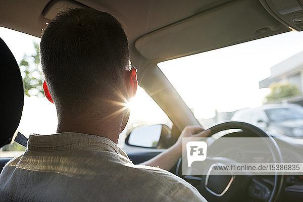Rückansicht eines jungen Mannes  der bei Sonnenuntergang Auto fährt