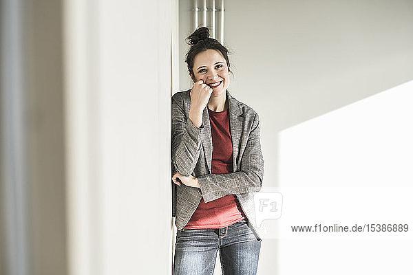 Porträt einer lächelnden Geschäftsfrau  die im Büro an eine Wand gelehnt ist