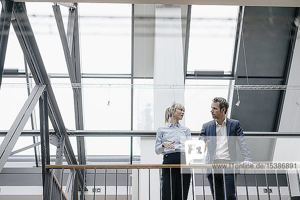 Geschäftsmann und -frau stehen im Bürogebäude und diskutieren