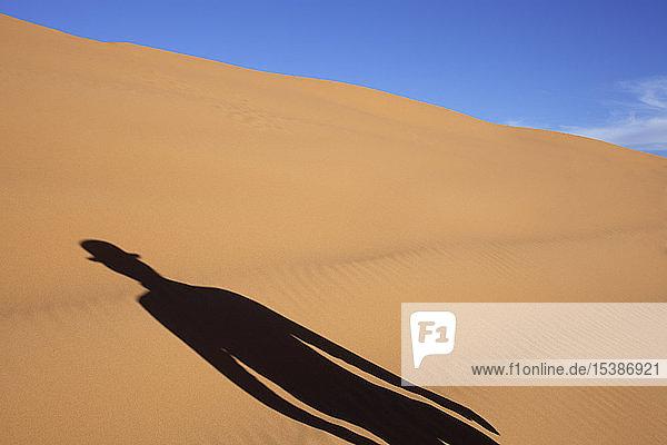 Morocco  Merzouga  Erg Chebbi  shadow of man wearing a bowler hat in desert dune