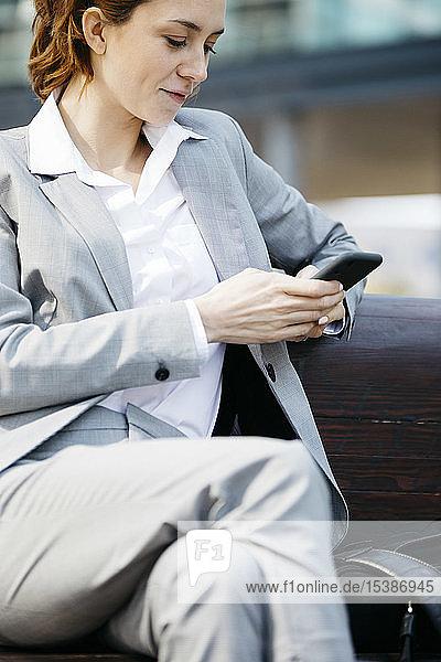Junge Geschäftsfrau  die auf einer Bank in der Stadt sitzt und ein Smartphone benutzt