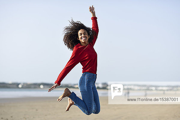 Carefree young woman jumping on the beach