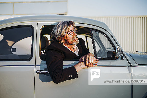 Älterer Mann lehnt sich aus dem Fenster eines Oldtimers