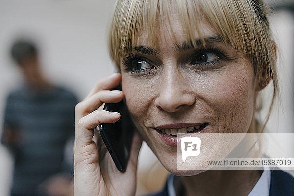 Geschäftsfrau am Telefon  Kollegin im Hintergrund
