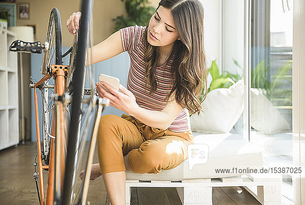 Young woman with cell phone reparing bicycle at home