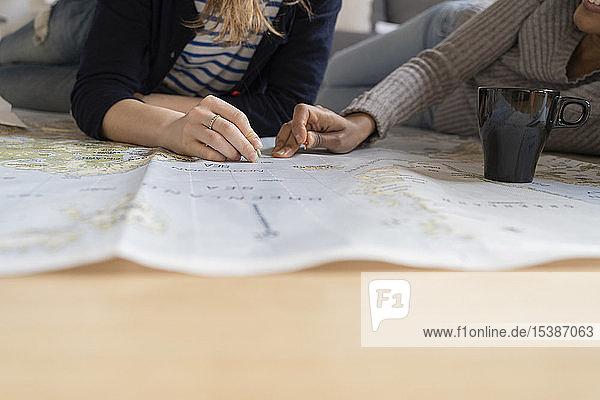 Freunde stecken Stecknadeln auf eine Landkarte  planen ihren Urlaub  machen dicht