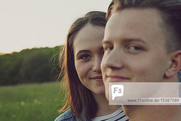 Porträt einer glücklichen Teenagerin  die sich hinter ihrem Freund versteckt