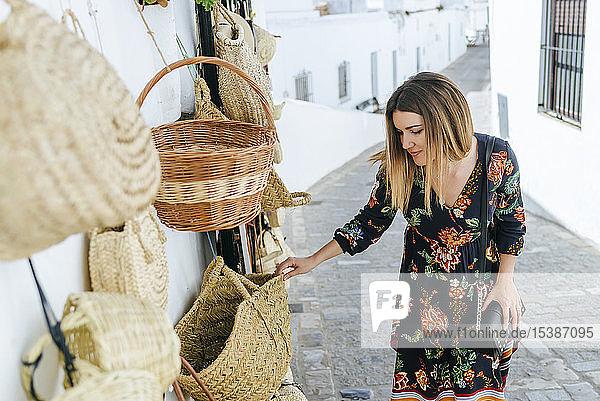 Spanien  Cádiz  Vejer de la Frontera  modische Frau  die in einem Geschäft Taschen und Körbe betrachtet