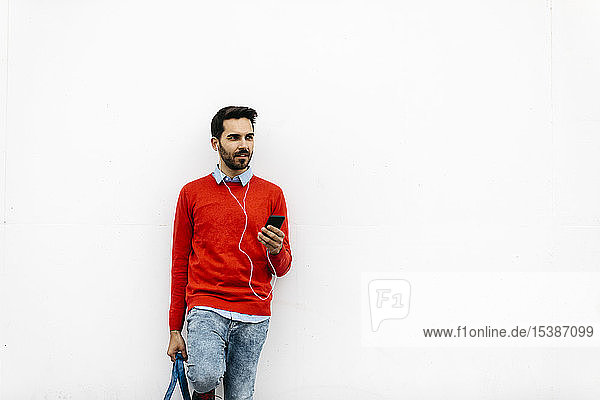 Casual businessman leaning on wall  using earphones and smartphone