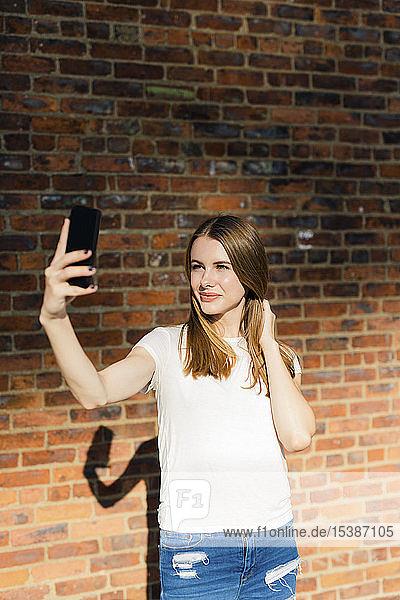 Junge Frau vor einer Ziegelmauer  die Smartphone-Selfie