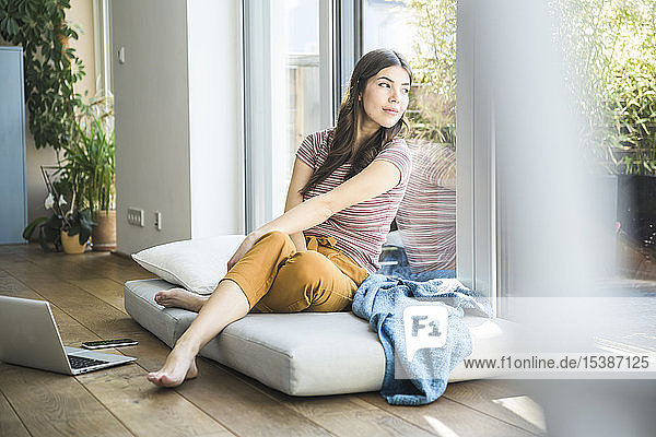 Young woman sitting at the window at home with laptop