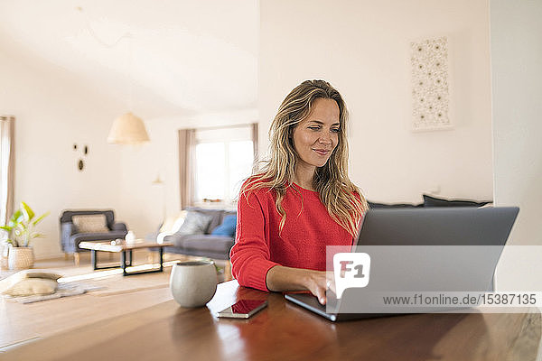 Woman using laptop on dining table at home
