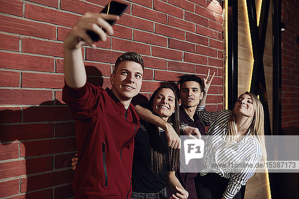 Happy friends taking a selfie with smartphone at brick wall