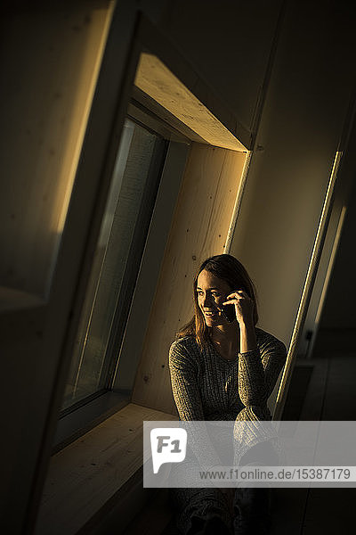 Frau sitzt bei Sonnenuntergang am Bürofenster und telefoniert