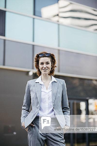 Porträt einer erfolgreichen jungen Geschäftsfrau in der Stadt  mit Händen in den Taschen