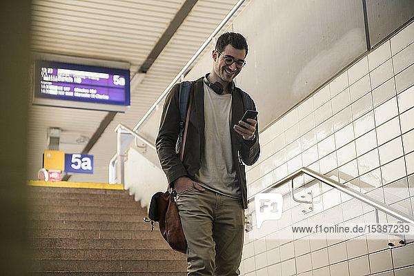 Lächelnder junger Mann mit Handy geht am Bahnhof die Treppe hinunter