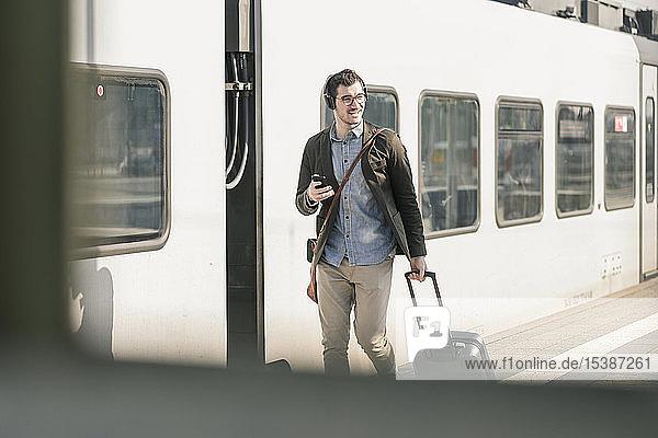 Lächelnder junger Mann mit Kopfhörern  Handy und Koffer auf dem Bahnsteig