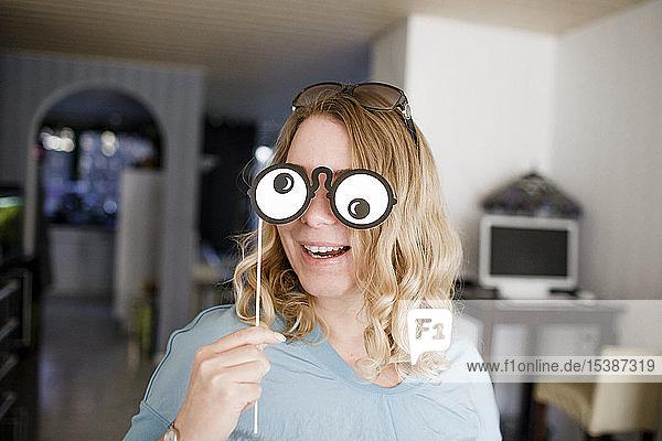 Blonde Frau  die die Augen mit einer komischen Maske bedeckt