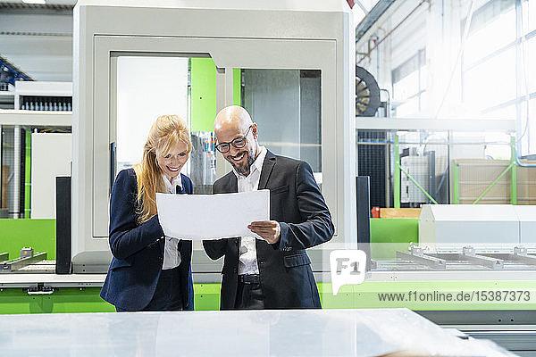 Lächelnder Geschäftsmann und Geschäftsfrau betrachten Plan in Fabrik
