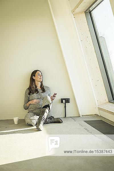 Schwangere Frau trinkt Tee und sitzt auf dem Boden ihres neuen Hauses