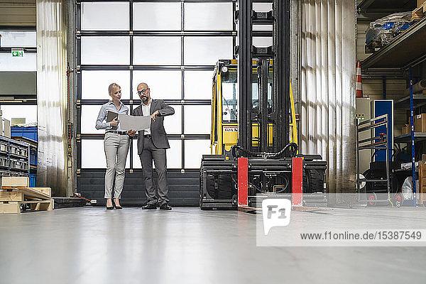 Geschäftsmann und Geschäftsfrau besprechen Plan in Fabrik
