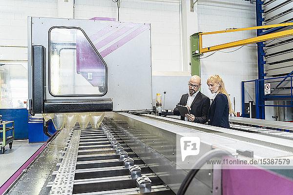 Geschäftsmann und Geschäftsfrau mit Tablette am Fließband in der Fabrik