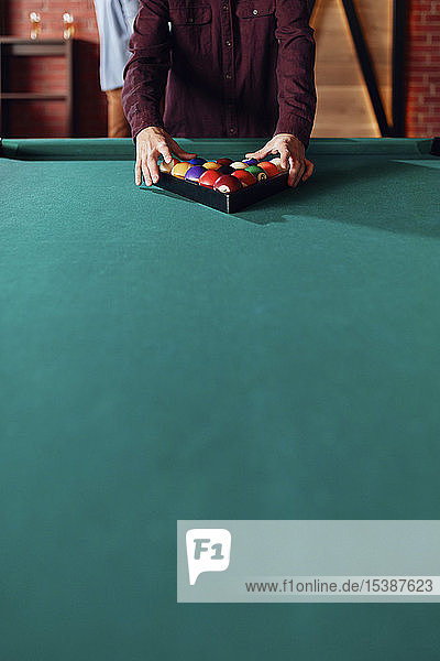 Close-up of billiards player arranging balls on table