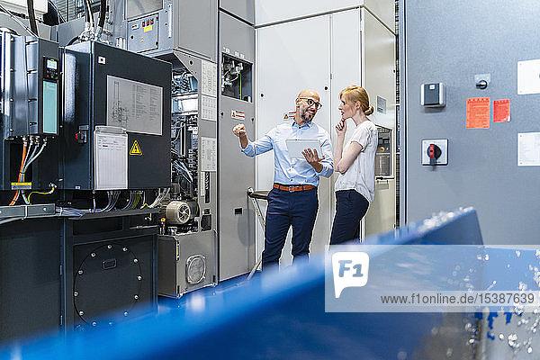 Geschäftsmann mit Tablette zeigt Geschäftsfrau in Fabrik Maschine
