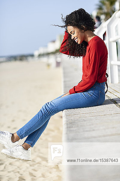 Happy young woman sitting on beach promenade