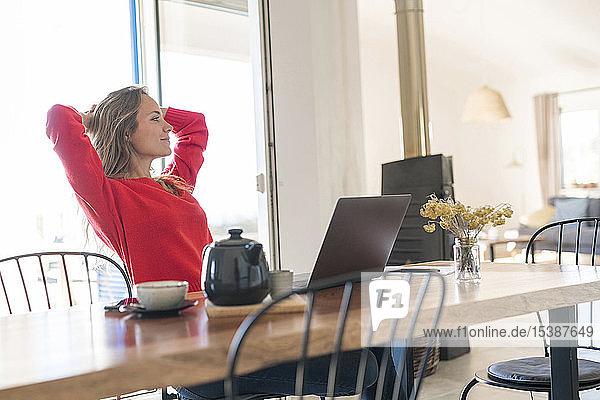 Frau mit Laptop auf dem Esstisch zu Hause  die eine Pause macht
