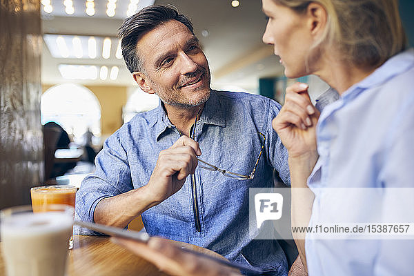 Smiling man and woman with tablet in a cafe