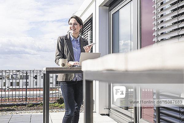 Lächelnde Geschäftsfrau mit Handy und Laptop auf der Dachterrasse