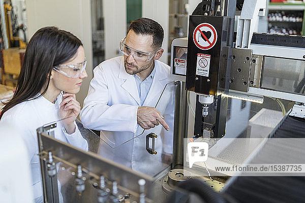 Kollegen tragen Laborkittel und Schutzbrille an der Maschine in einer modernen Fabrik
