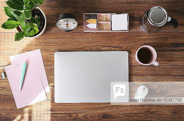 Geschlossener Laptop  Kaffeetasse und andere Utensilien auf dem Schreibtisch im Heimbüro  Draufsicht