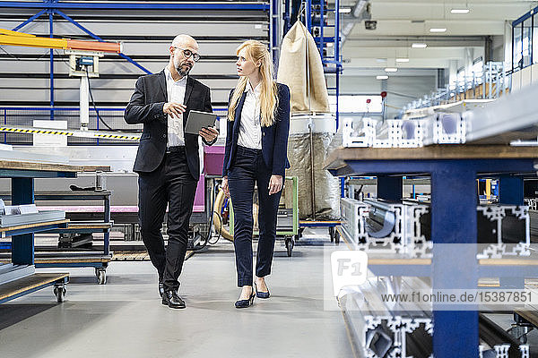 Geschäftsmann und Geschäftsfrau mit Tablette in der Fabrik