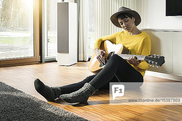 Woman sitting on the floor of living room playing guitar