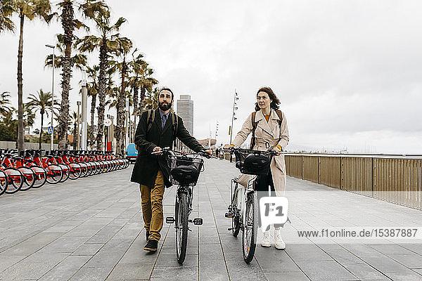 Ehepaar schiebt E-Bikes an der Strandpromenade