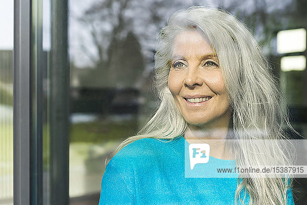 Portrait of happy mature woman looking out of window