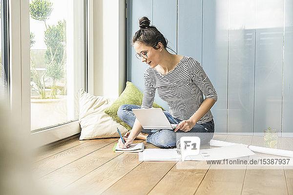 Frau sitzt zu Hause am Fenster und macht Notizen