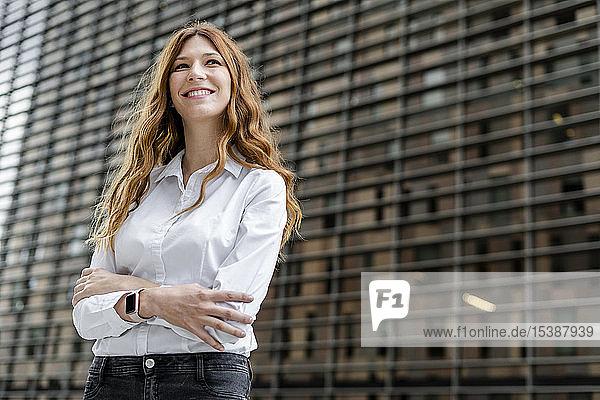 Junge Businessfrau in der Stadt  mit verschränkten Armen  Porträt