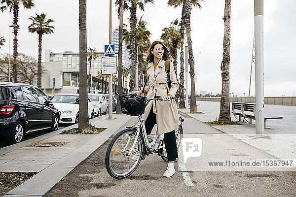 Lächelnde Frau mit E-Bike auf einer Promenade