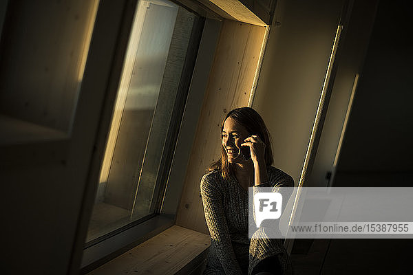 Woman sitting at office window at sunset  talking on the phone