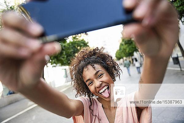 Unbekümmerte junge Frau  die in der Stadt ein Selfie betreibt