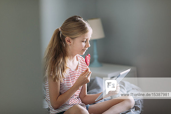 Blondes Mädchen sitzt mit Lolli auf dem Bett und benutzt ein digitales Tablett