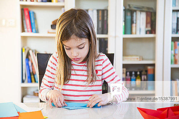 Girl tinkering with paper on table at home