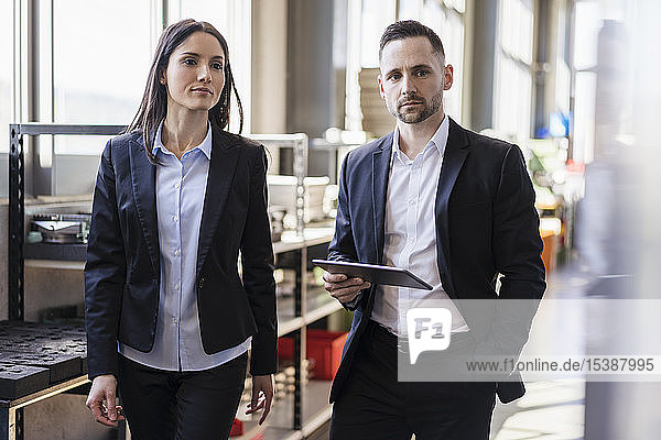 Businessman and businesswoman with tablet in modern factory
