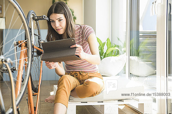 Young woman with tablet reparing bicycle at home
