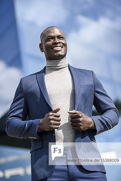 Portrait of content businessman wearing blue suit and grey turtleneck pullover