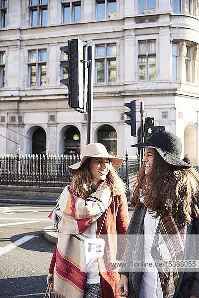 UK  London  two happy women in the city crossing a street
