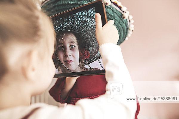 Kleines Mädchen  das eine verkleidete Schwester mit Tablette fotografiert
